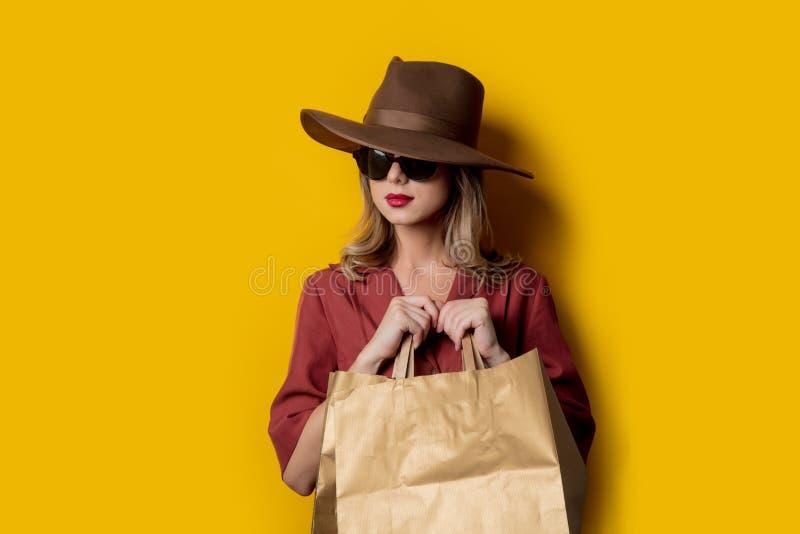 Elegant kvinna i solglasögon och med shoppingpåsar fotografering för bildbyråer