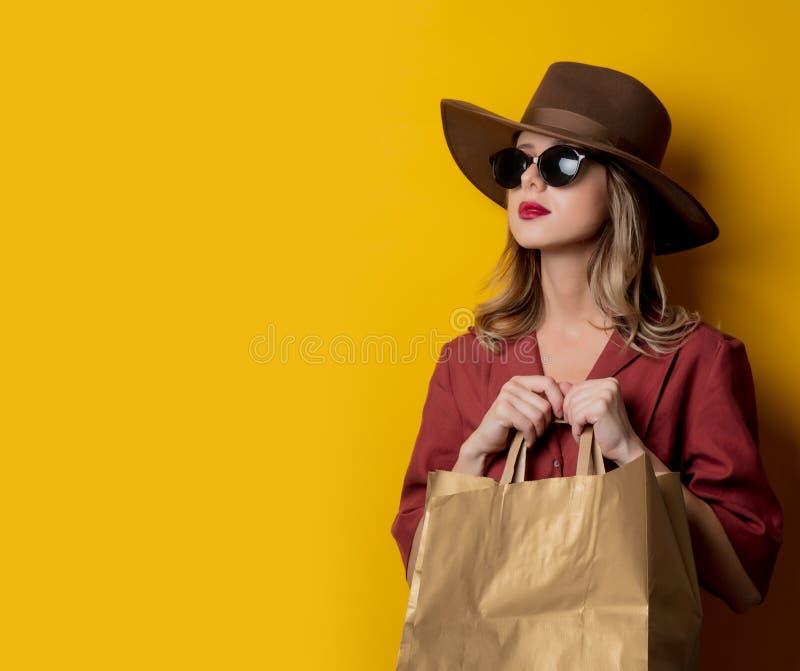 Elegant kvinna i solglasögon och med shoppingpåsar arkivbild