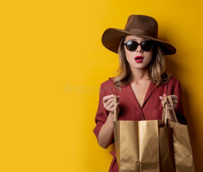 Elegant kvinna i solglasögon och med shoppingpåsar royaltyfria foton