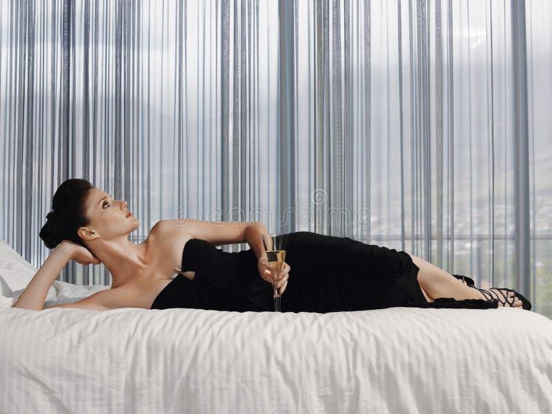 Elegant kvinna med Champagne Glass Lying In Bed arkivbild