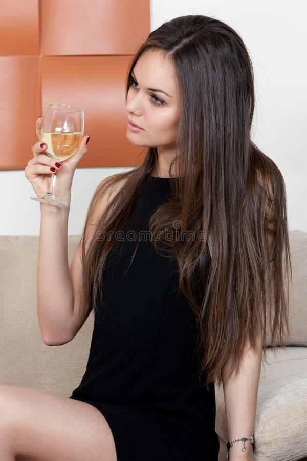 Elegant kvinna med ett exponeringsglas av vin royaltyfria foton