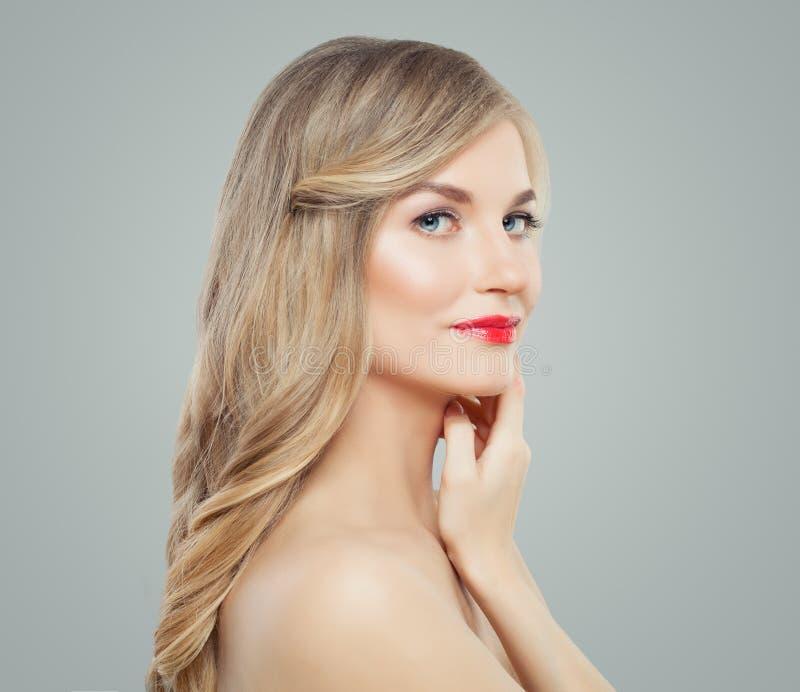 Elegant kvinna med långt blont lockigt hår, sund hud och röd kantmakeup Ansikts- behandling, håromsorg och cosmetologybegrepp fotografering för bildbyråer
