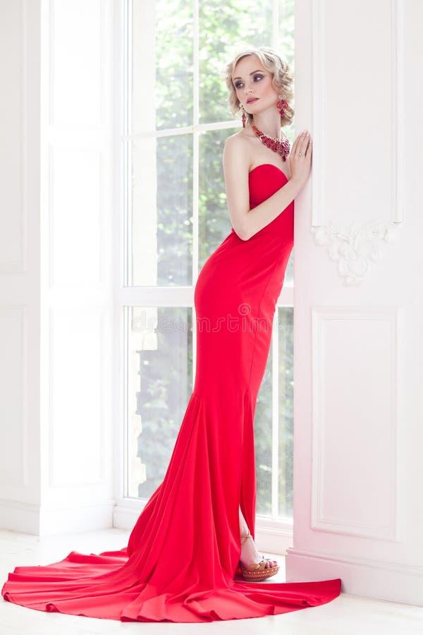 Elegant kvinna med perfekt makeup och röda långa klänningen som poserar nea royaltyfri foto