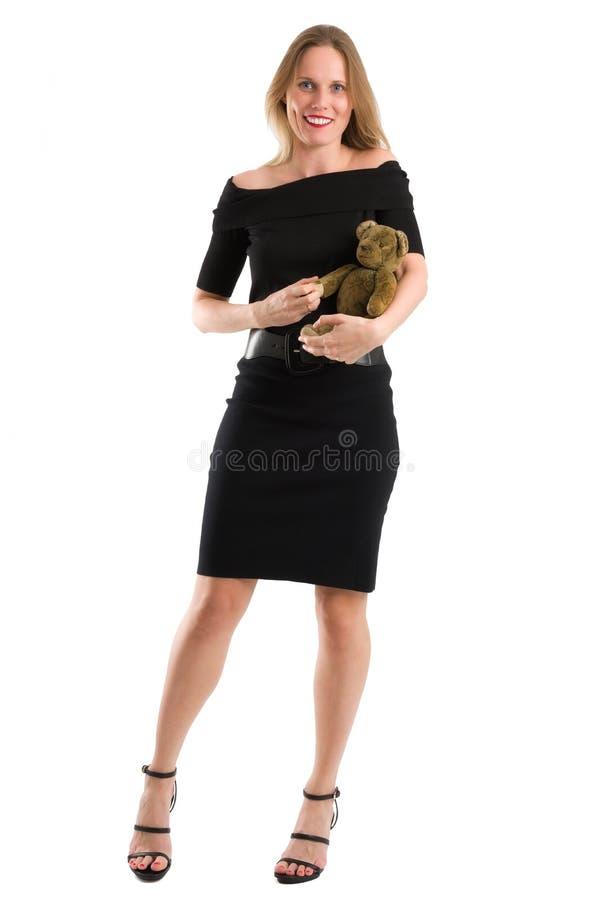 Elegant kvinna som canoodling hennes antika nalle som isoleras på vit royaltyfri bild