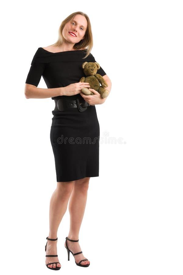 Elegant kvinna som canoodling hennes antika nalle som isoleras på vit royaltyfri foto