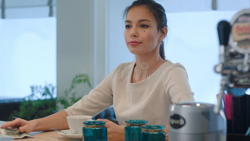 Elegant kvinna som frågar för en räkning, medan sitta på kaféräknaren royaltyfri fotografi