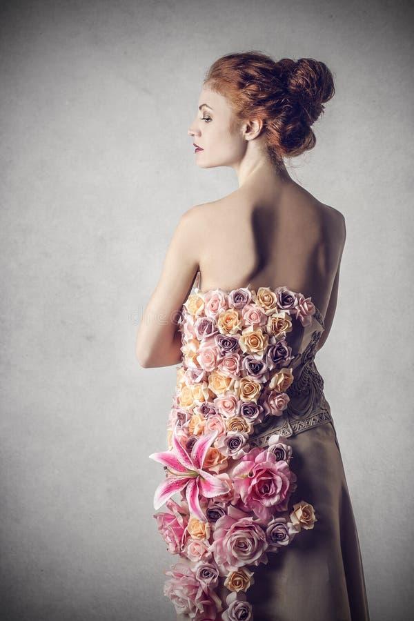 Elegant kvinna som kläs med blommor arkivfoton