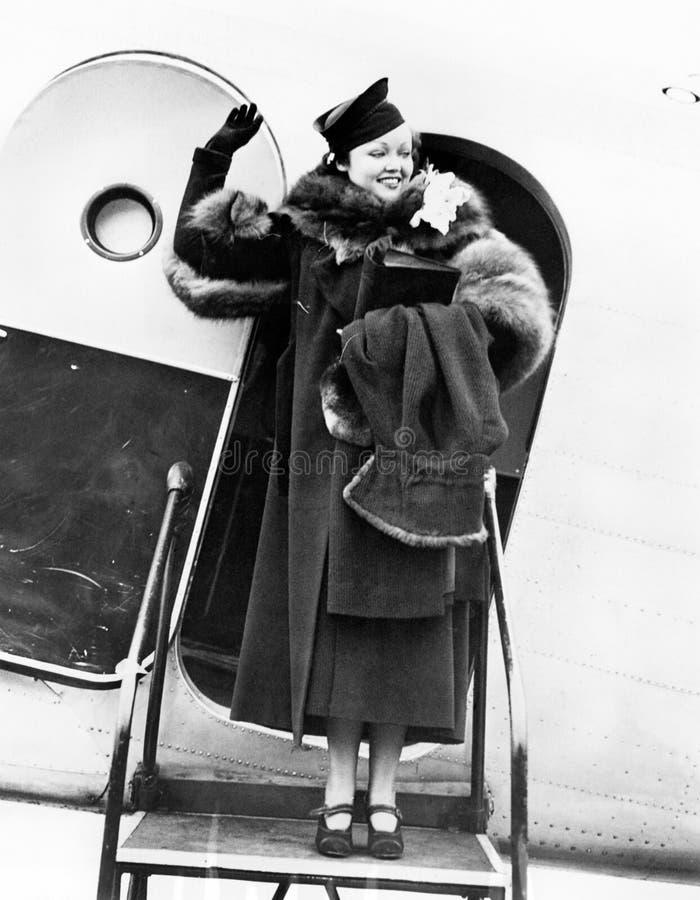 Elegant kvinna som kliver ut ur ett flygplan, och vinka (alla visade personer inte är längre uppehälle, och inget gods finns Leve royaltyfria foton