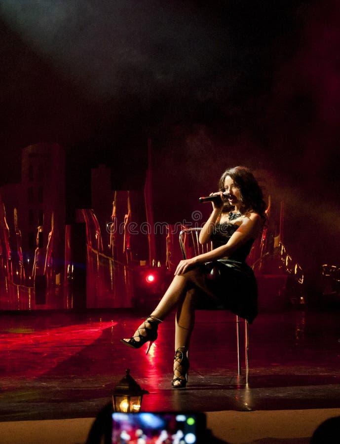 Elegant kvinna som sjunger i färgglad rök, slut upp royaltyfri foto