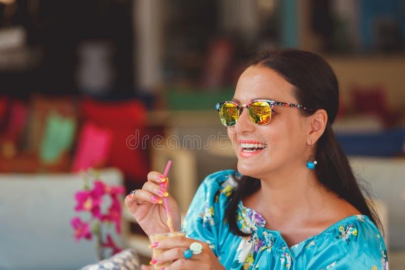 Elegant kvinna som tycker om med is kaffe på ett kafé royaltyfri fotografi