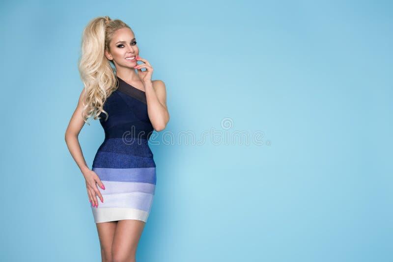 Elegant kvinnlig modell i ett anseende för mini- klänning på en blå bakgrund royaltyfri fotografi