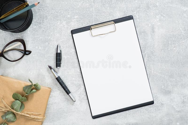Elegant kvinnligt skrivbord med tom papperskartong, presentlåda med förgrening av eukalyptus, glasögon på stenbakgrund Hemkontor arkivbild