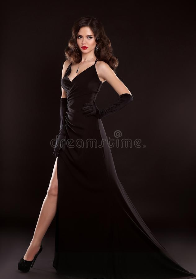 Elegant lady in black dress. fashion studio photo of gorgeous woman with retro wavy hair style and evening makeup, in long gown w. Ith gloves on black background royalty free stock photography