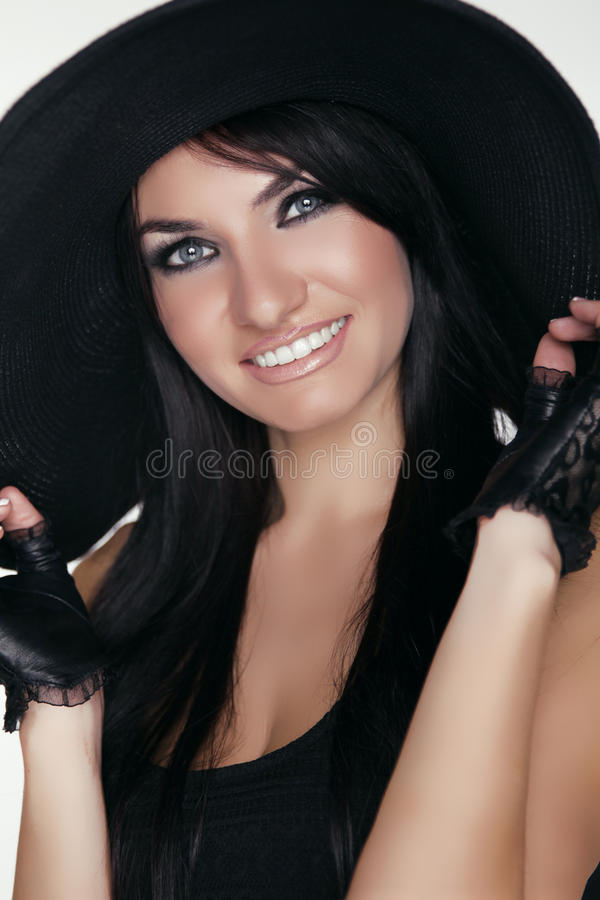 Elegant lady. Happy smiling brunette woman model posing in black. Hat isolated on white background. Vogue style stock photos