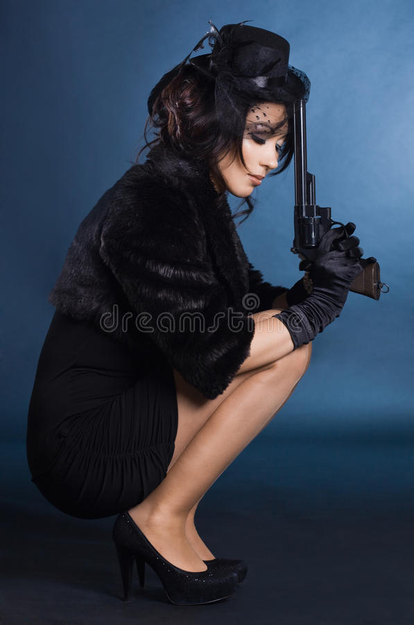Elegant lady with a pistol stock photography