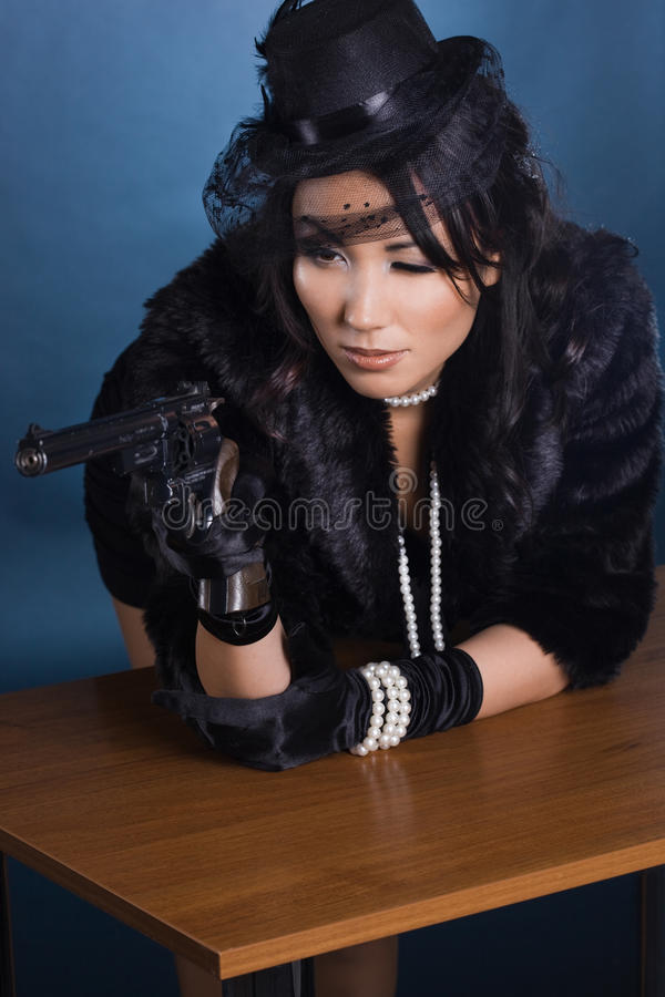 Elegant lady with a pistol stock photos