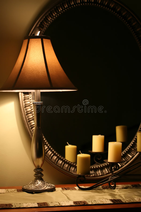 Elegant Lamp and Mirror. A cozy interior still life with lamp, candles and mirror royalty free stock images
