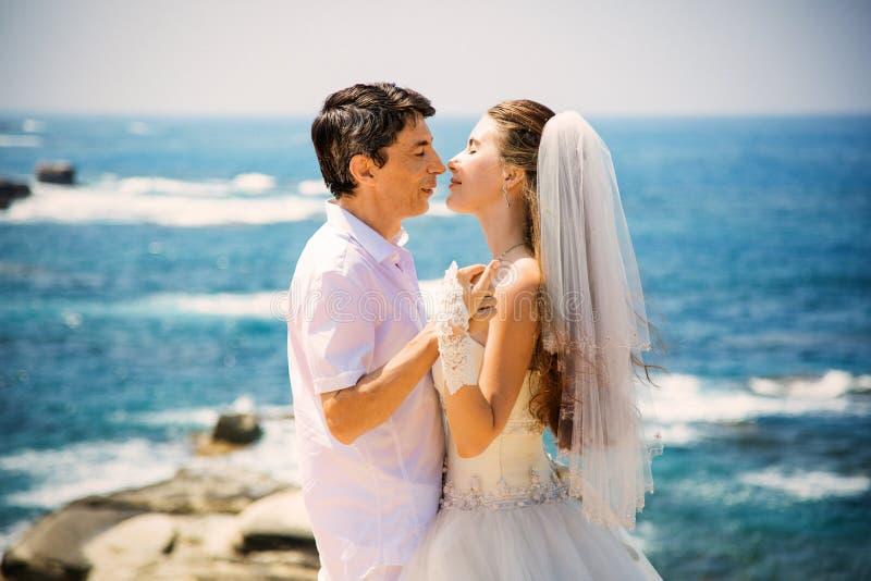 Elegant le brud och brudgum som går på stranden som kysser, bröllopceremoni, medelhav arkivfoto