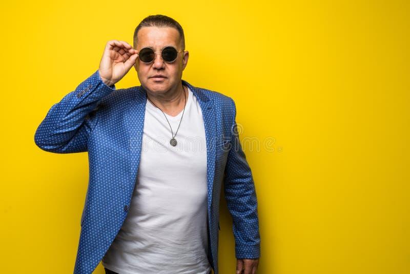 Elegant le mogen manstående som bär ett par av solglasögon som isoleras på gul bakgrund fotografering för bildbyråer