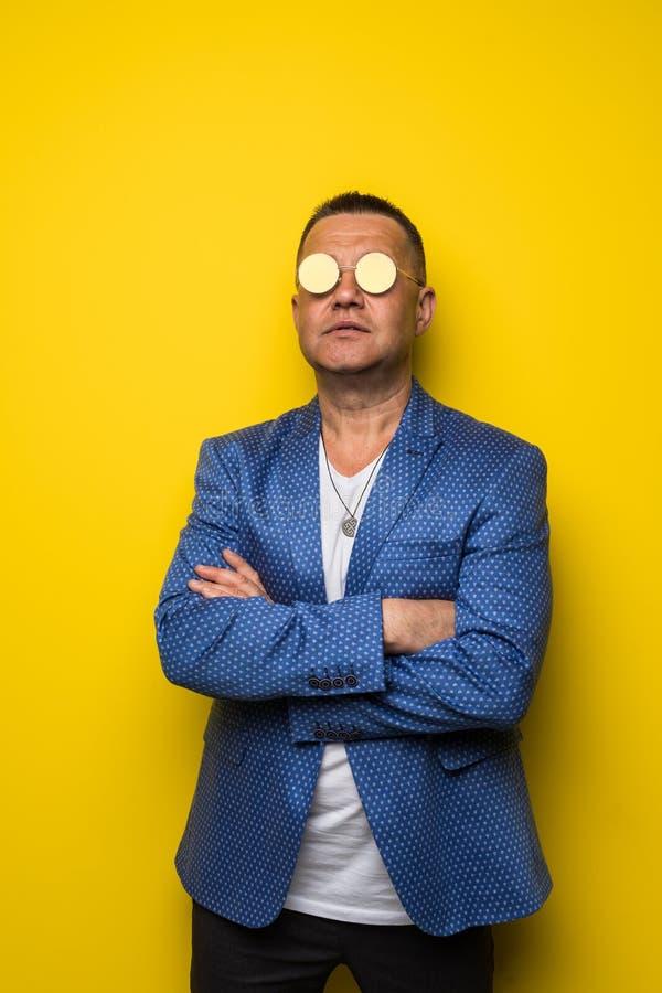 Elegant le mogen manstående som bär ett par av solglasögon som isoleras på gul bakgrund arkivbild