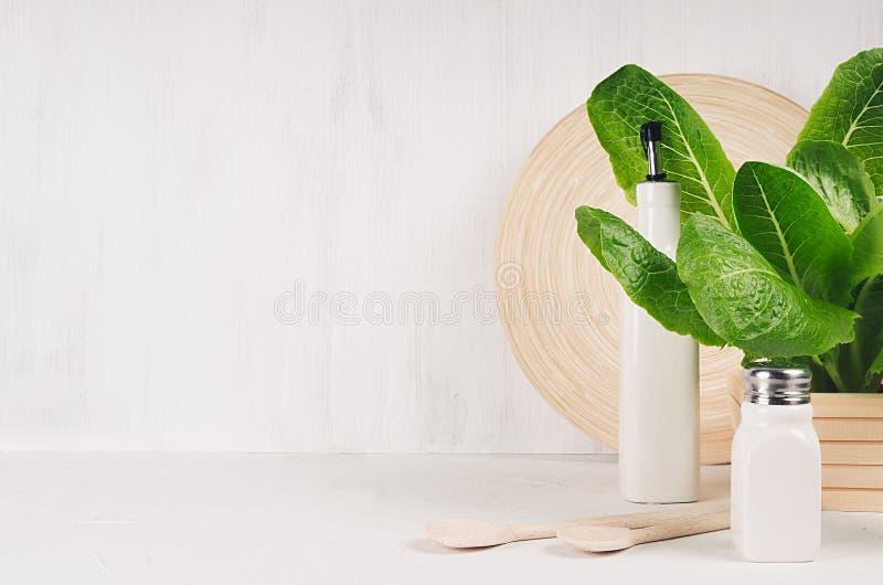 Elegant licht keukenbinnenland met houten werktuigen, keramiek en groene bladerengreens op witte houten plank royalty-vrije stock foto's