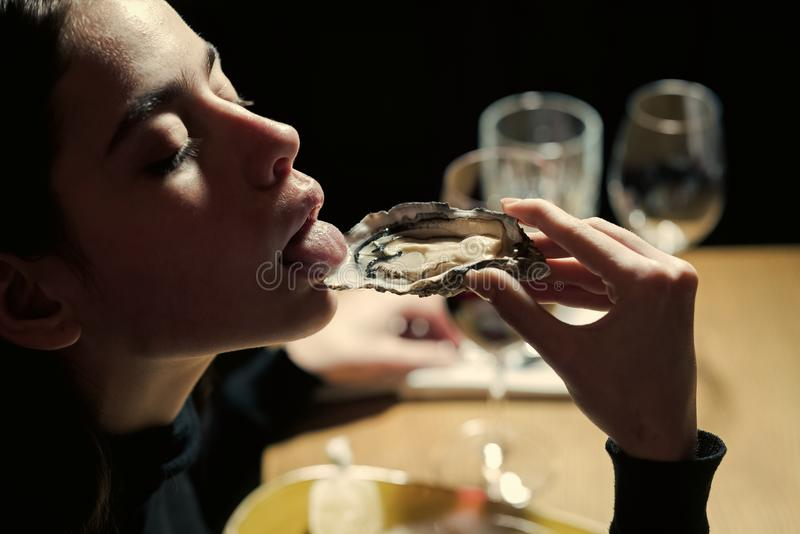 Elegant life. Dieting and health. Seafood and Mediterranean cuisine with mussels in shell. Woman eating shellfish. Young. Woman eating oyster in luxury stock photos