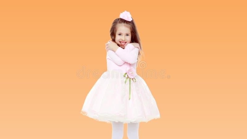 Elegant liten flicka i en rosa klänning arkivfoton