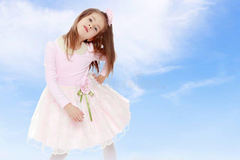 Elegant liten flicka i en rosa klänning arkivbilder