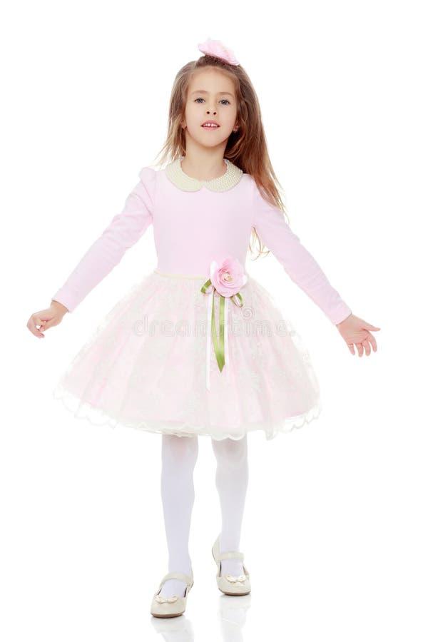 Elegant liten flicka i en rosa klänning royaltyfri foto
