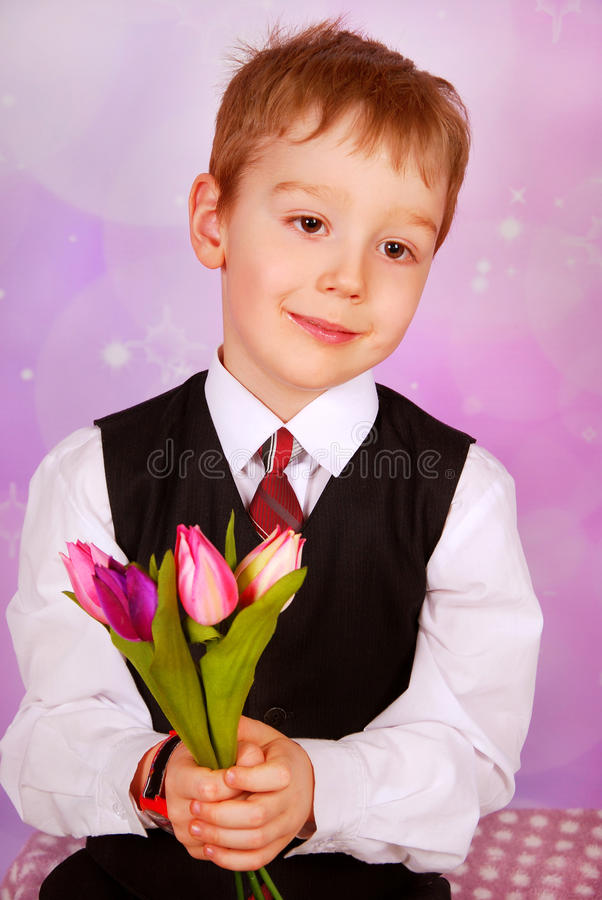 Elegant little boy with bunch of tulips