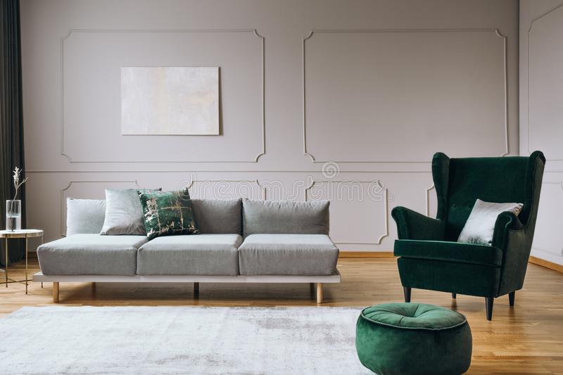 Elegant room interior with emerald green chair with pillow and long grey couch. Elegant living room interior with emerald green chair with pillow and long grey stock photo