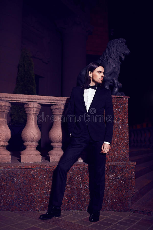 Elegant long-haired young caucasian muscled attractive handsome man model businessman in black costume with moustache in the stock image