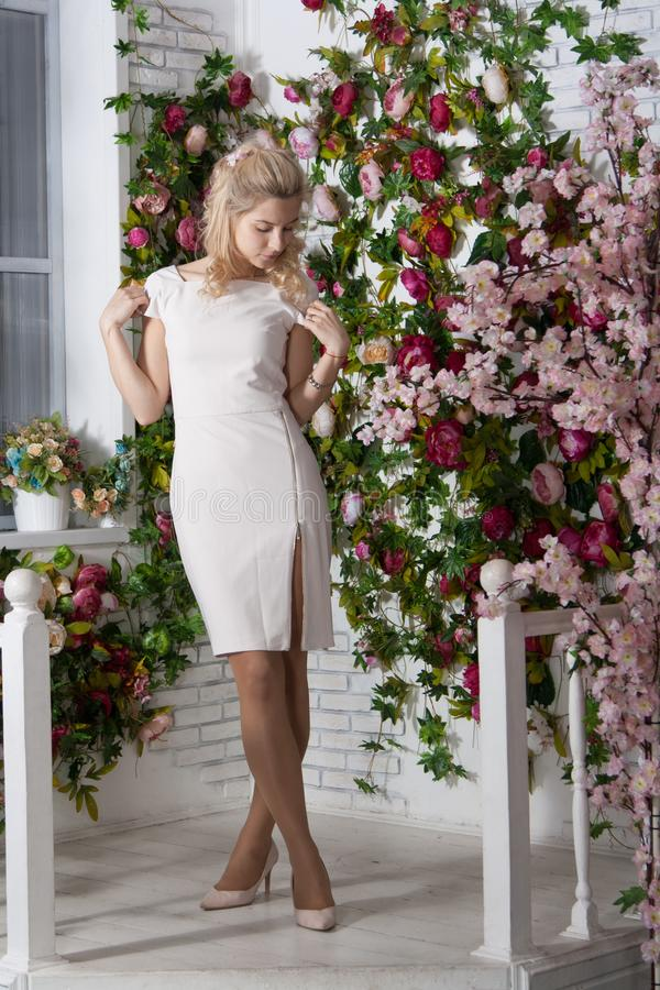 Elegant long-legged young woman against a brick wall with flowers. Full length portrait of attractive young woman in white short. Beautiful lady in white dress stock image