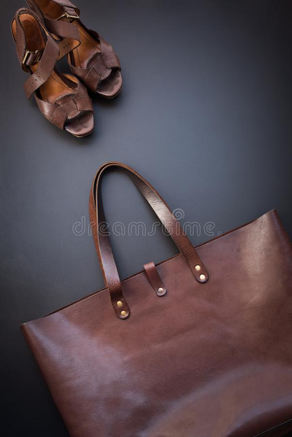 Elegant luxury brown female leather bag and shoes. On dark background. Rich bussines accessory. Object flat lay top view copy space. Sales fashion concept stock photo
