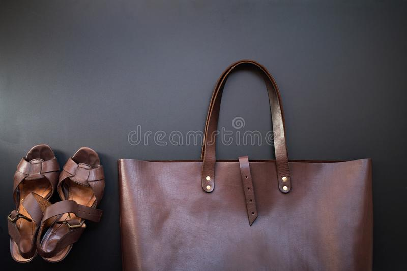 Elegant luxury brown female leather bag and shoes. On dark background. Rich bussines accessory. Object flat lay top view copy space. Sales fashion concept royalty free stock photo