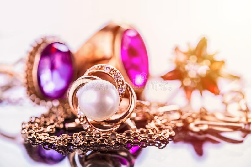 Elegant luxury composition of gold jewelry with pearl ring, amethysts and rubys gemstones on light background close-up macro and stock photo