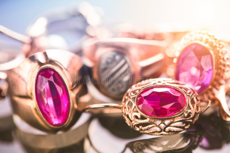Elegant luxury composition of gold jewelry with ring with red amethyst and ruby gemstone and diamonds on light background close-up royalty free stock photos