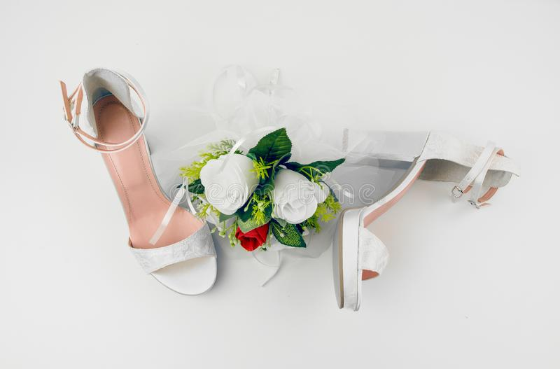 Elegant Luxury Laced Bridal Wedding Shoes And Bouquet With Red R. Ose On White Background royalty free stock images