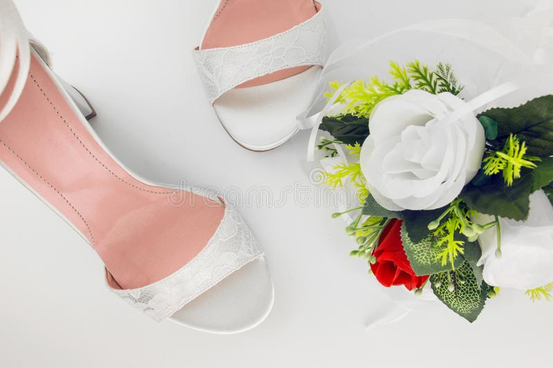 Elegant Luxury Laced Bridal Wedding Shoes And Bouquet With Red R. Ose On White Background royalty free stock image