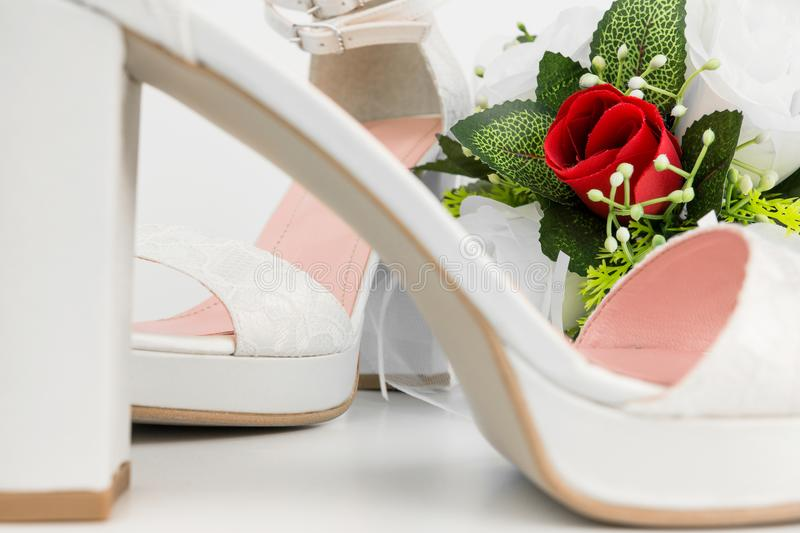 Elegant Luxury Laced Bridal Wedding Shoes And Bouquet With Red R. Ose On White Background stock photography