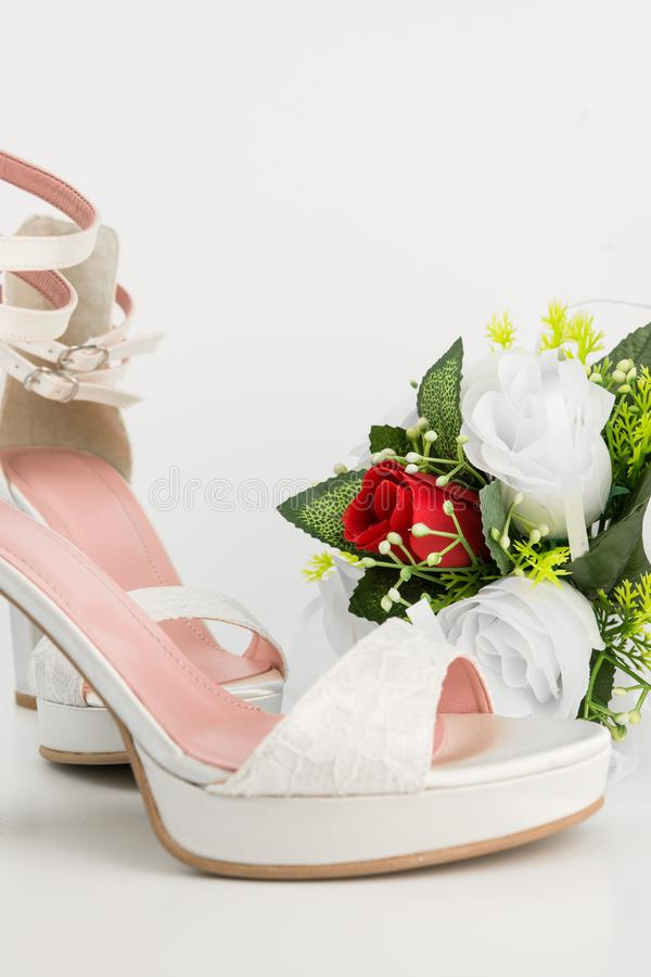 Elegant Luxury Laced Bridal Wedding Shoes And Bouquet With Red R. Ose On White Background stock image
