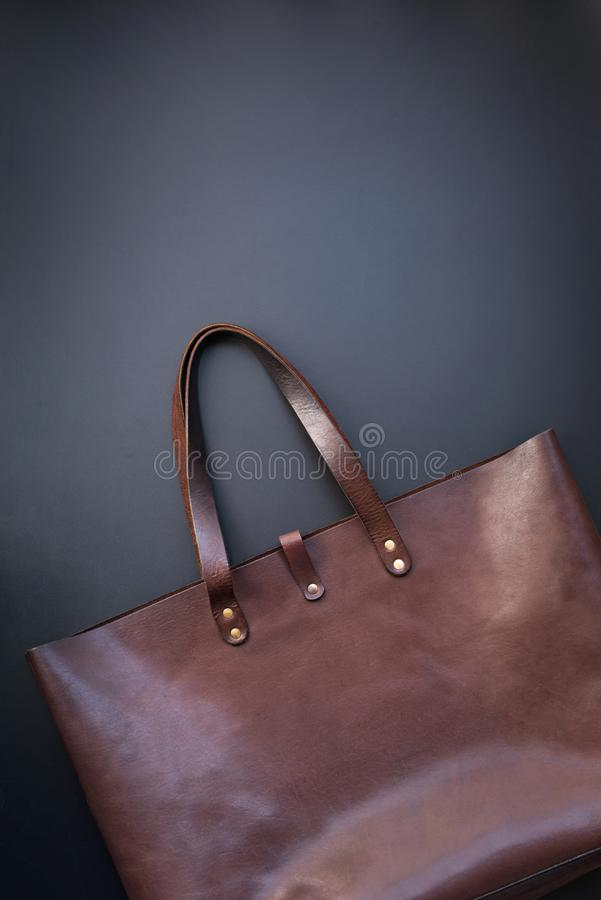 Elegant luxury leather brown bag dark background. Elegant luxury leather brown bag on dark background. Rich bussines female accessory. Object flat lay top view royalty free stock images