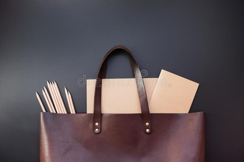 Elegant luxury office set note books leather bag. Elegant luxury office set with note books pencils rubber in brown leather bag on dark background. Rich bussines stock image