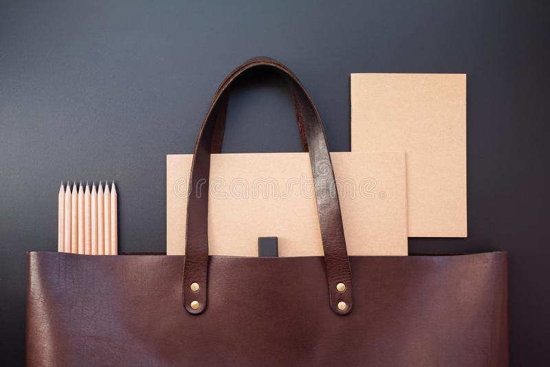 Elegant luxury office set note books leather bag. Elegant luxury office set with note books pencils rubber in brown leather bag on dark background. Rich bussines stock images