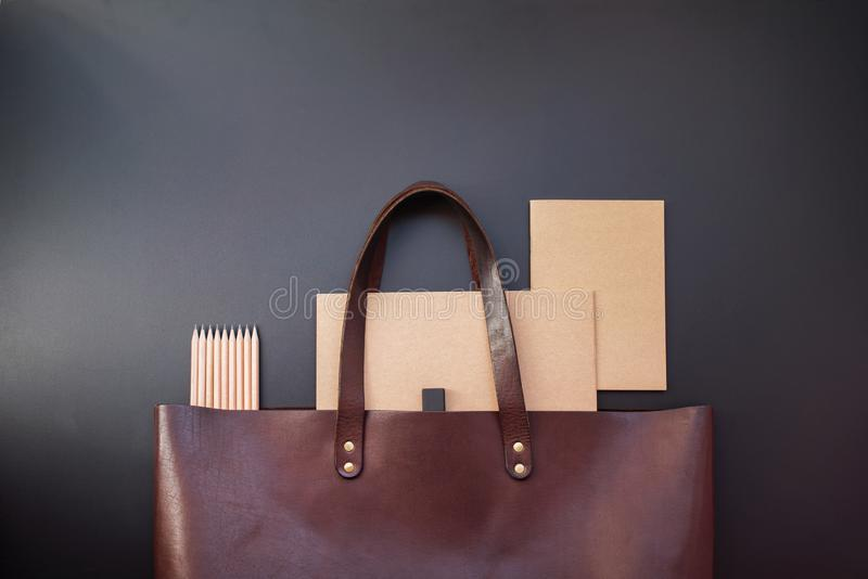 Elegant luxury office set note books leather bag. Elegant luxury office set with note books pencils rubber in brown leather bag on dark background. Rich bussines royalty free stock photo