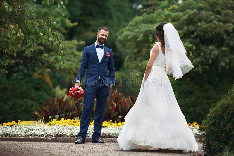 Elegant lycklig brud i härlig klänning som går in mot att le G royaltyfri foto
