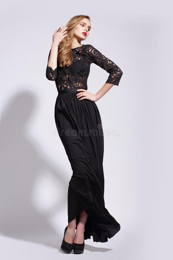 Elegant lyxig kvinna som poserar i lång klänning royaltyfri fotografi