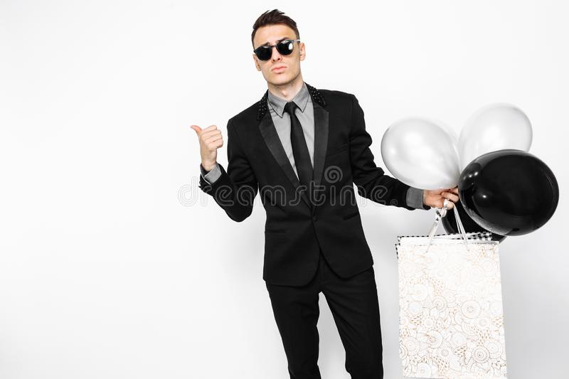 An elegant man in a black suit, with bags in his hands, and ball. An elegant man, in a black suit, with bags in his hands, and balloons, looks at the empty space stock photo