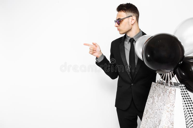 An elegant man in a black suit, with bags in his hands, and ball. An elegant man, in a black suit, with bags in his hands, and balloons, looks at the empty space royalty free stock images