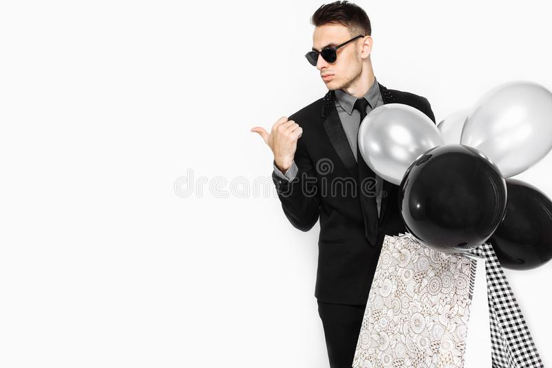 An elegant man in a black suit, with bags in his hands, and ball. An elegant man, in a black suit, with bags in his hands, and balloons, looks at the empty space royalty free stock photos